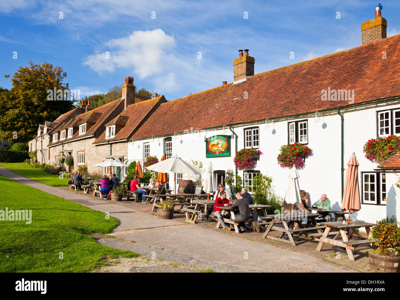 People sat outside The Tiger Inn on the village green East Dean East Sussex England UK GB EU Europe - Stock Image