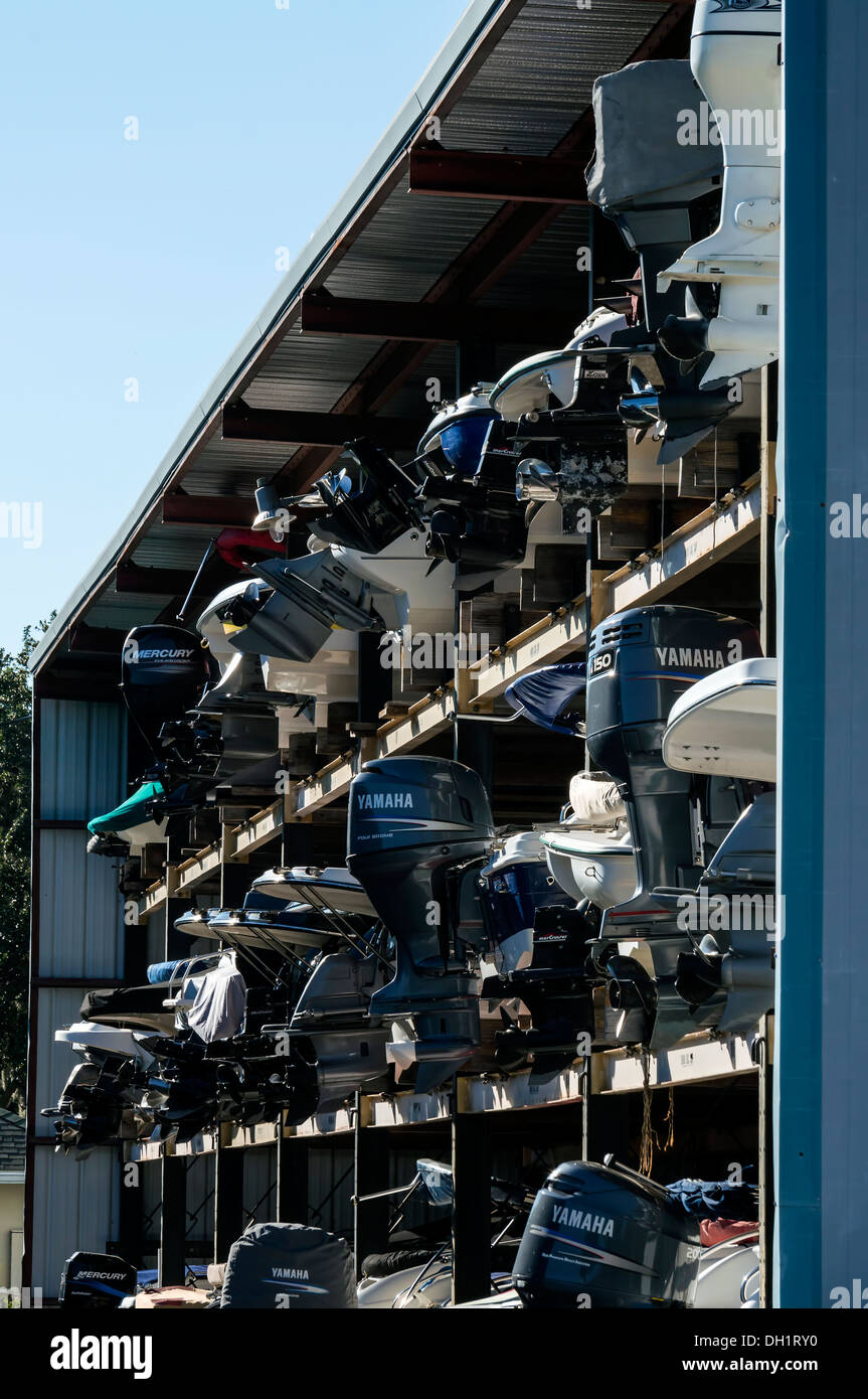 Speed boats with outboard motors engines stacked in dry dock in a steel frame metal building in Mount Dora, Florida. - Stock Image