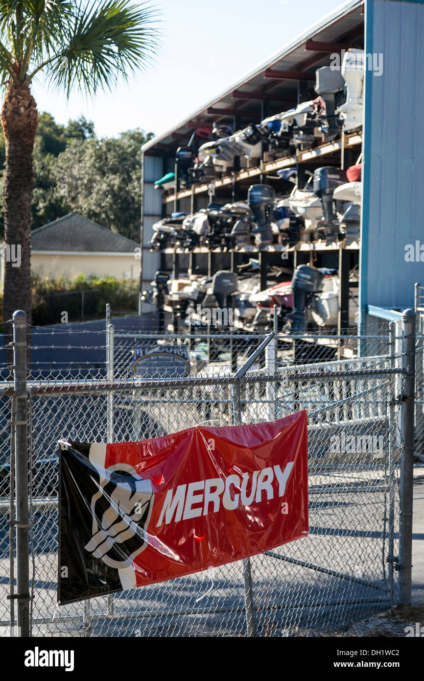 Mercury Marine logo on banner and speed boats with outboard motors engines stacked in dry dock in a steel frame metal building. - Stock Image
