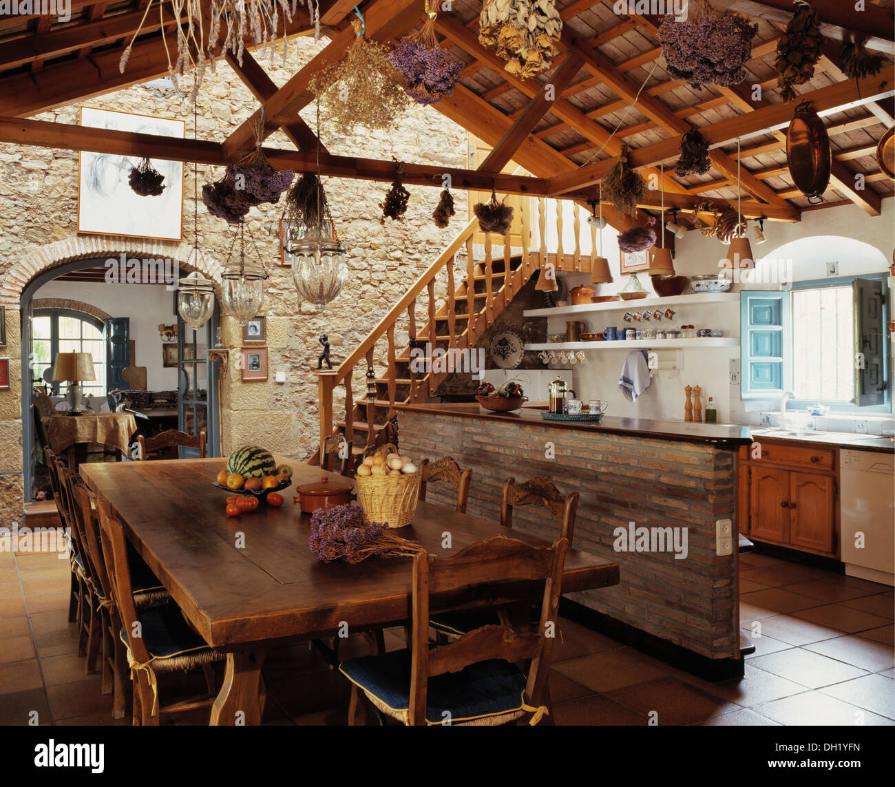 Rustic Wooden Table And Chairs In Dining Area Of Large Spanish Kitchen With  Dried Flowers Hanging From Wooden Ceiling Beams