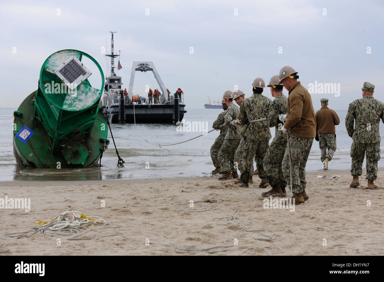 Navy sailors from Amphibious Construction Battalion 2, Beachmaster Unit 2, and Naval Beach Group 2 out of Joint Expeditionary Base Little Creek work with the Coast Guard to remove two washed-ashore buoys from Chic's Beach and Oceanview areas of Virginia B - Stock Image