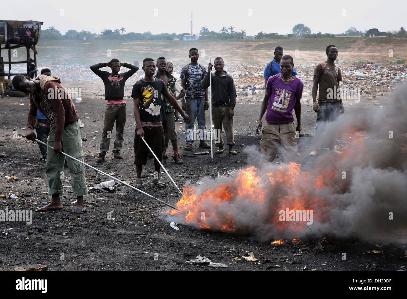 Teenage boys burn cables from computers and other electronics to recover copper near the Agbogbloshie slum in Accra, Ghana - Stock Image