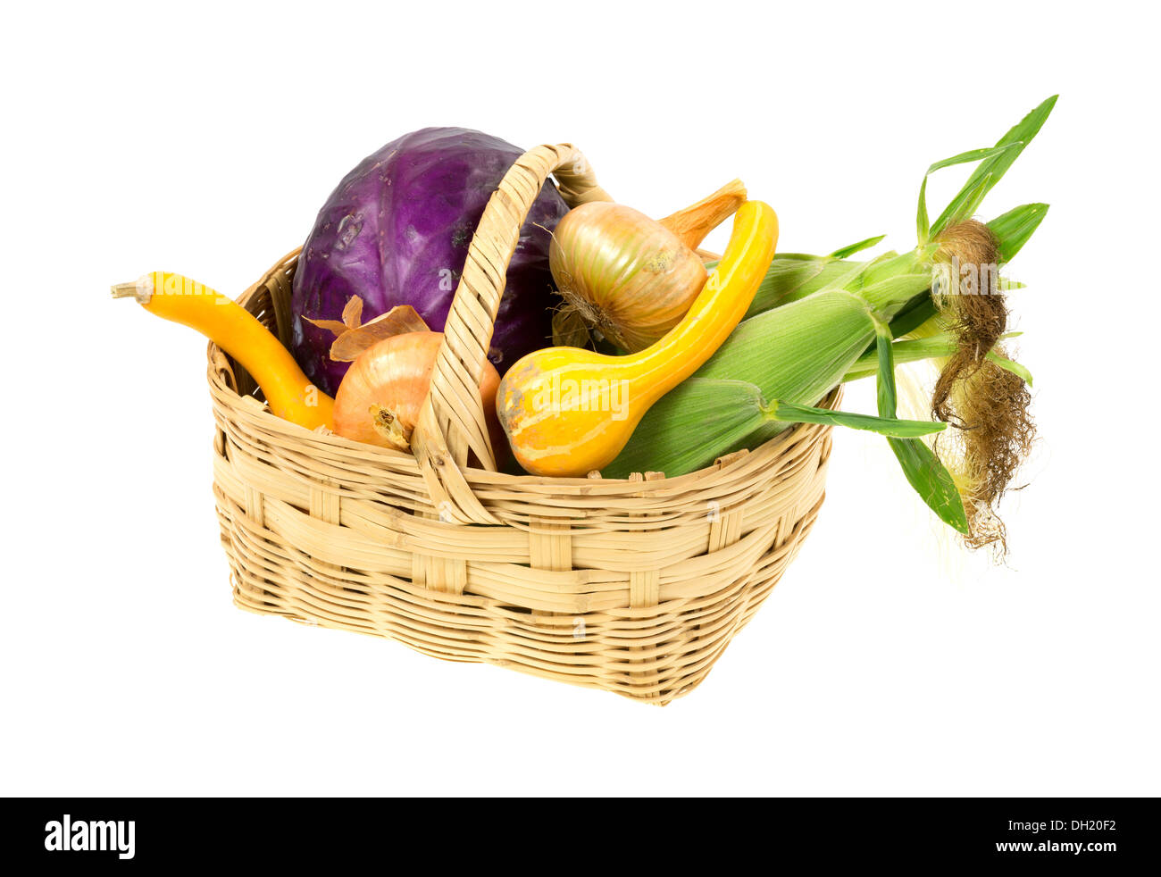 A large wicker basket filled with freshly picked assorted garden vegetables on a white background. Stock Photo