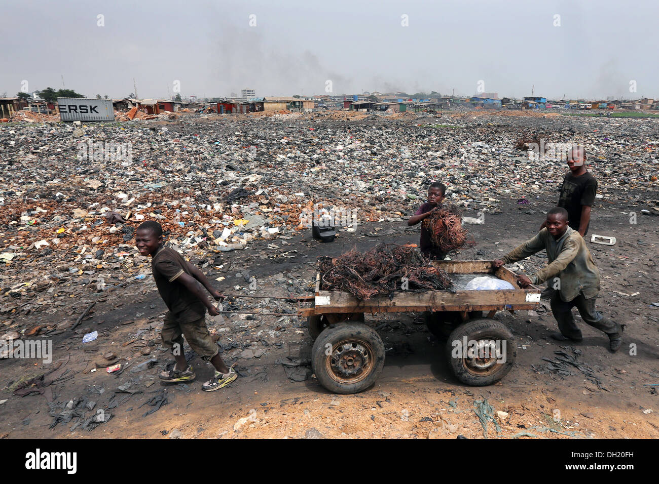 Boys pull a cart with raw copper cables from burned computers, Agbogbloshie dump site in Accra, Ghana - Stock Image