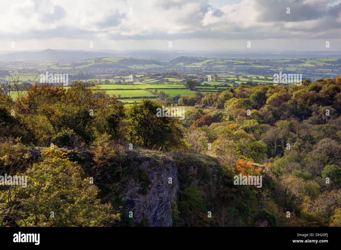 View from Ebbor Rock of the Somerset Levels and Glastonbury Tor in the mist with a dramatic sky - Stock Image