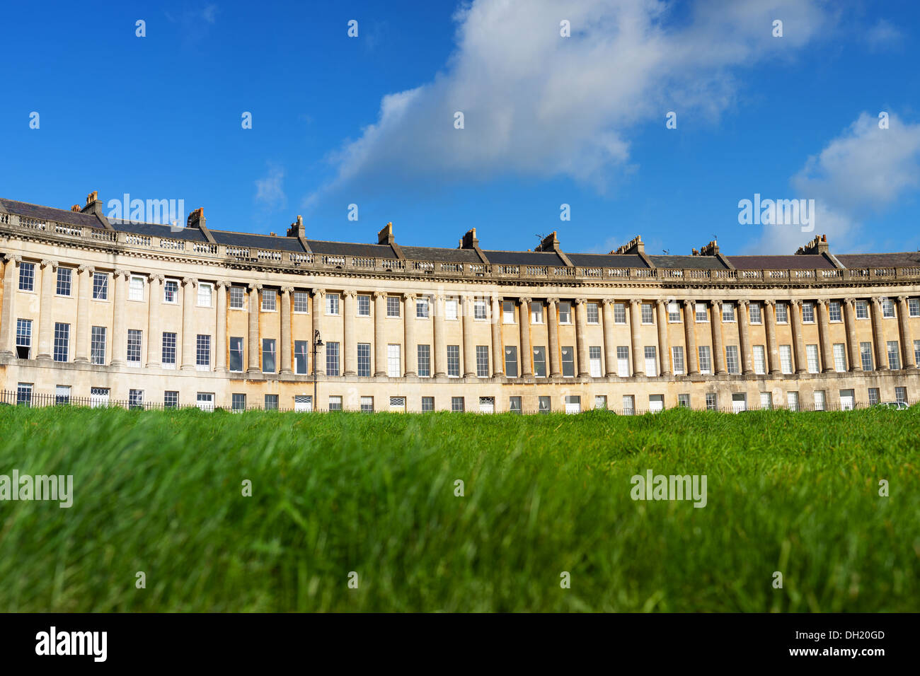 Low angle view of the Royal Crescent in Bath, Somerset with lush green lawn in the foreground. - Stock Image