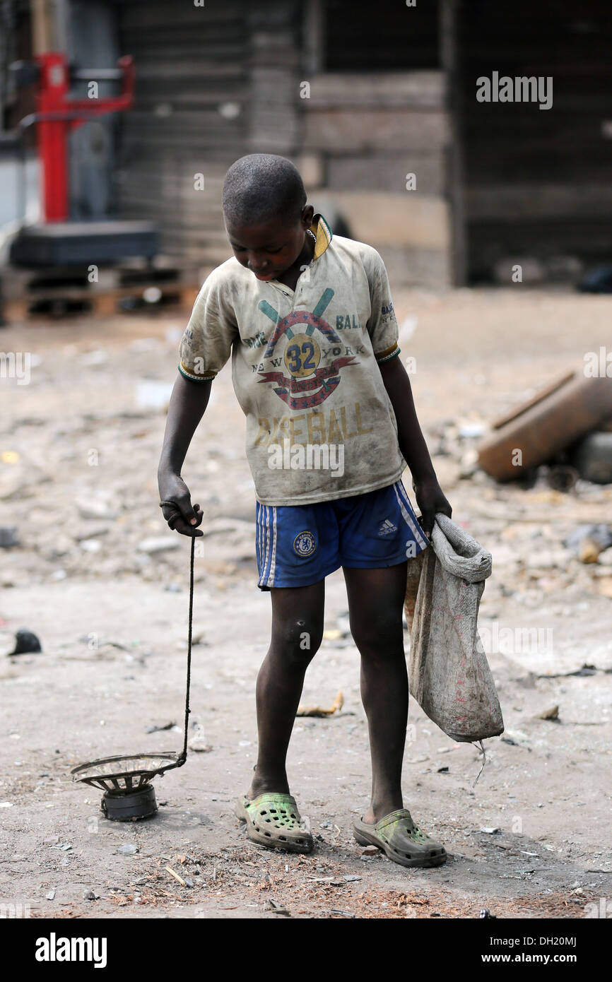 Boy collects iron parts with a magnet on the electronic garbage dump Agbogbloshie, Accra, Ghana - Stock Image