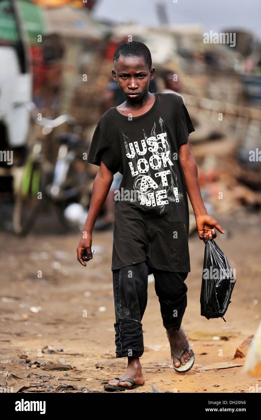 Young metal scrap collector at Agbogbloshie dump site wearing shirt JUST LOOK AT ME, Accra, Ghana - Stock Image