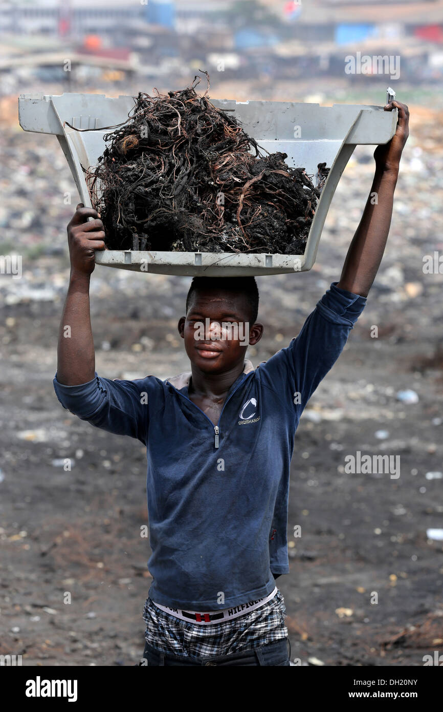 Teenage boy carries raw copper cables from burned computers, Agbogbloshie dump site in Accra, Ghana - Stock Image