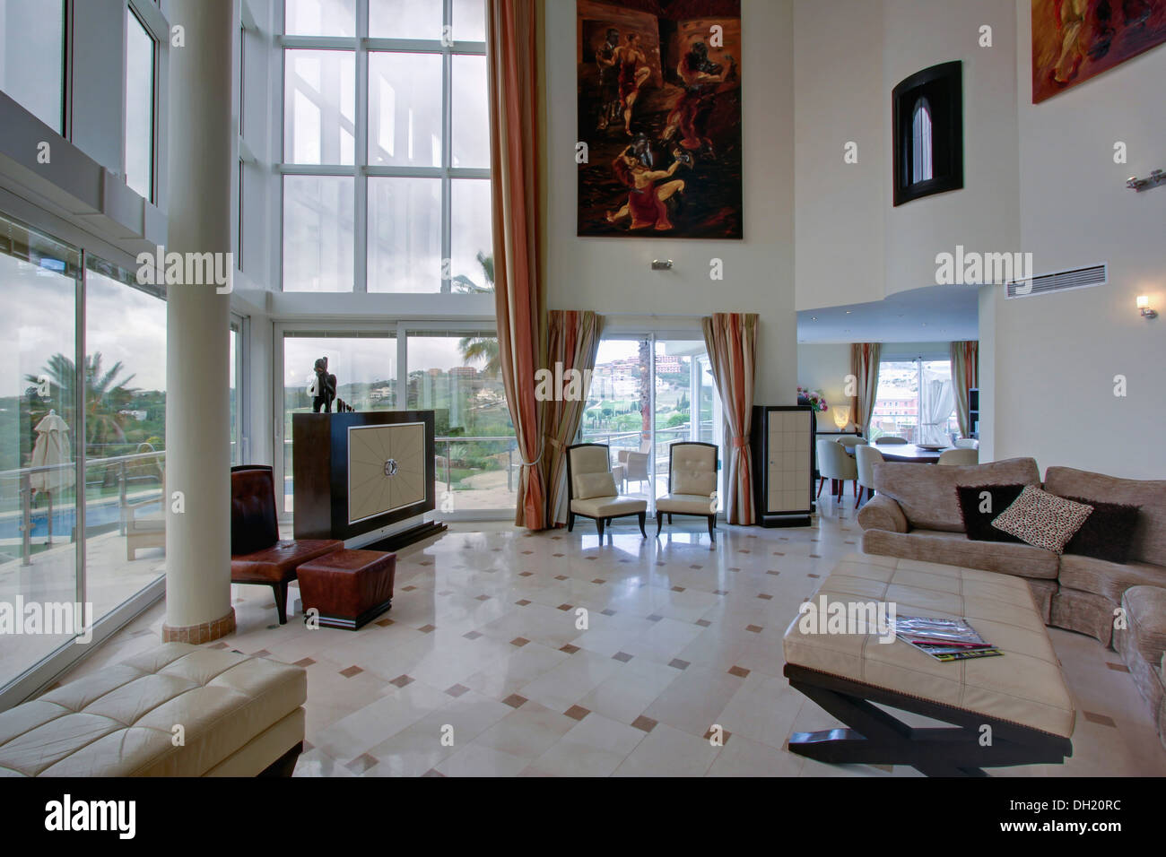 Large painting on wall of double height Spanish living room with