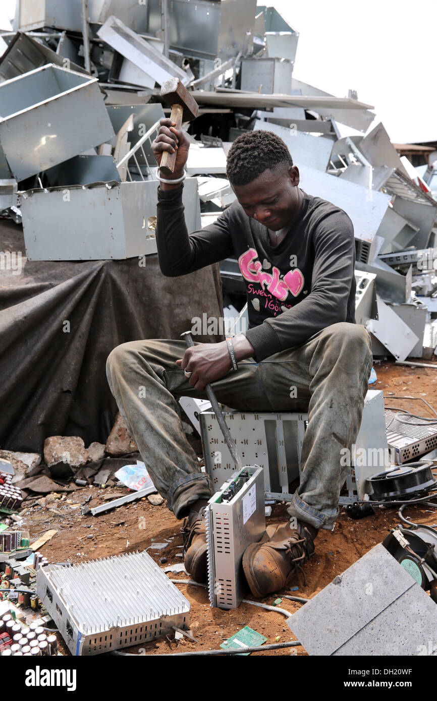 Teenage boys dismantle computer servers and other electronics to recover copper near the Agbogbloshie slum in Accra, Ghana - Stock Image