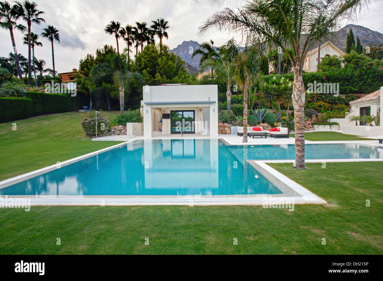 Large, turquoise swimming pool with small modern changing rooms and ...