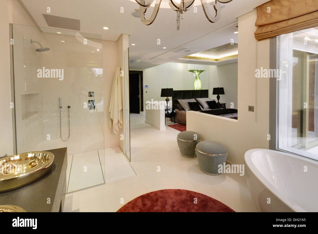 Large Walk In Shower And Gray Stools In Open Plan En Suite Bathroom In  Modern Spanish Apartment Bedroom