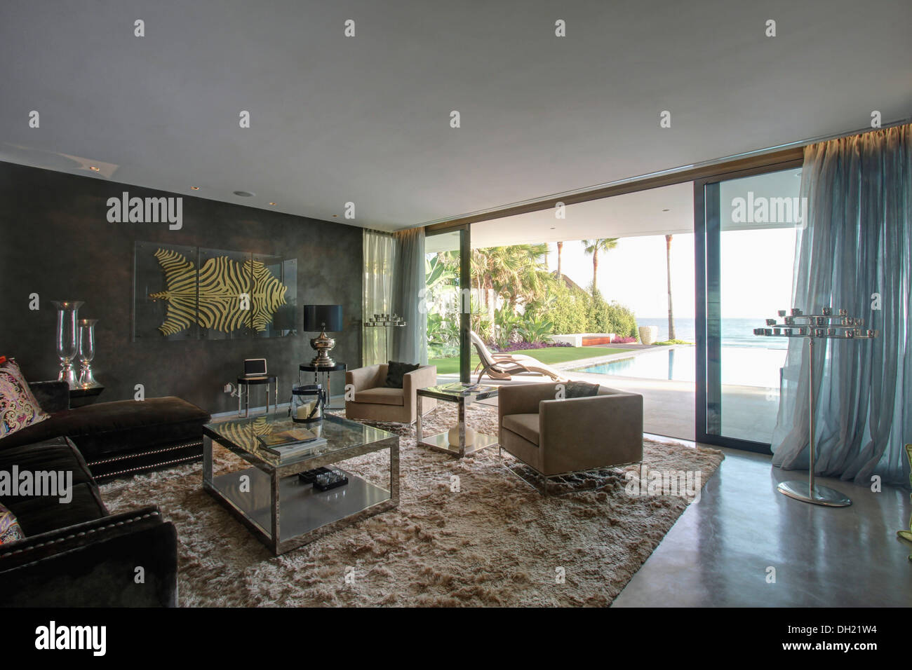 Armchairs and glass coffee table on shag pile carpet in modern Spanish living room with silver voile drapes on glass doors - Stock Image