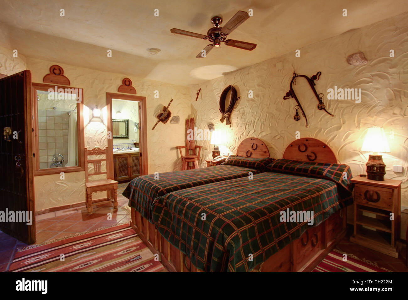 Electric Ceiling Fan Above Wooden Bed With Brown Checked Cover In Spanish  Bedroom With Rough Textured Walls And Door To En Suite