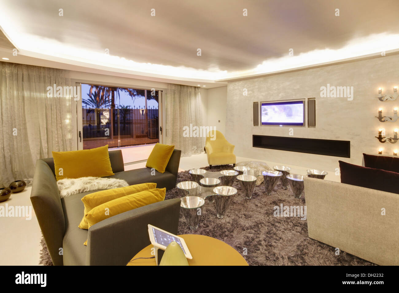 Yellow velvet cushions on gray sofas in large modern Spanish living room with shag pile carpet and chrome tables - Stock Image