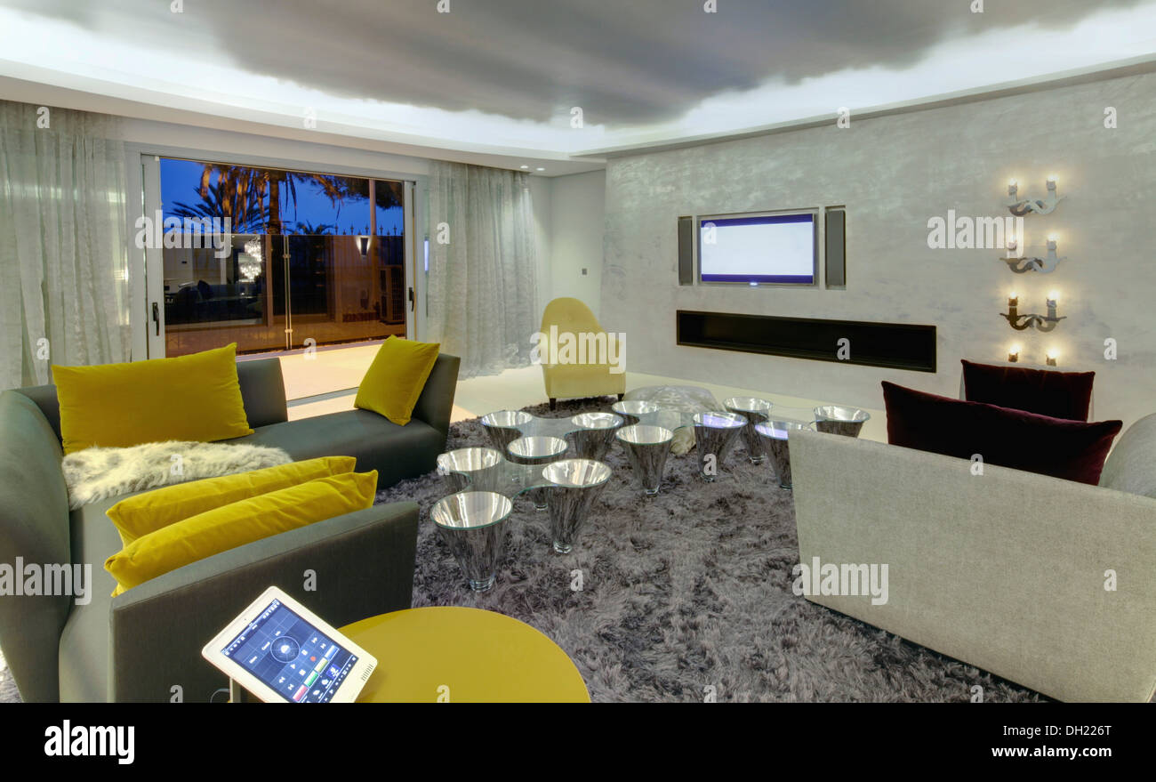 Yellow velvet cushions on gray sofas in modern Spanish living room with shag pile carpet and low conical chrome tables - Stock Image