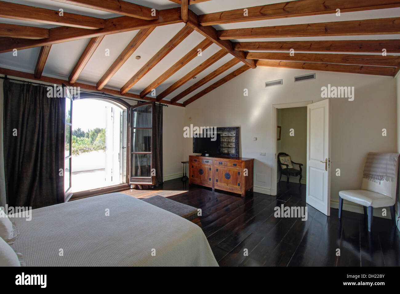 Polished Dark Wood Floor In Spanish Bedroom With Beamed Ceiling And Glass  Doors Open To Terrace