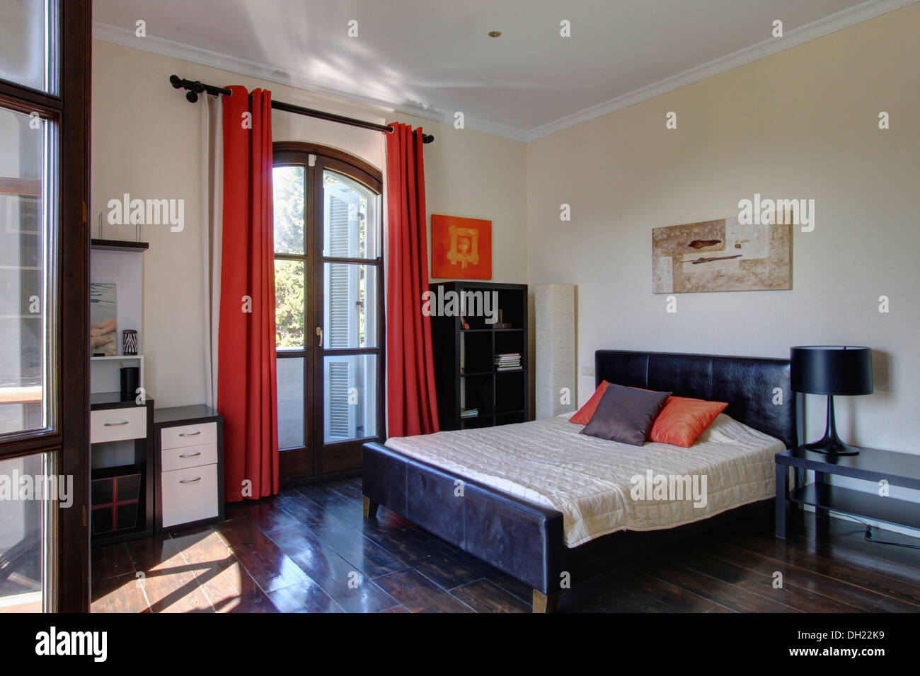 Red curtains on French windows in Spanish bedroom with black ...