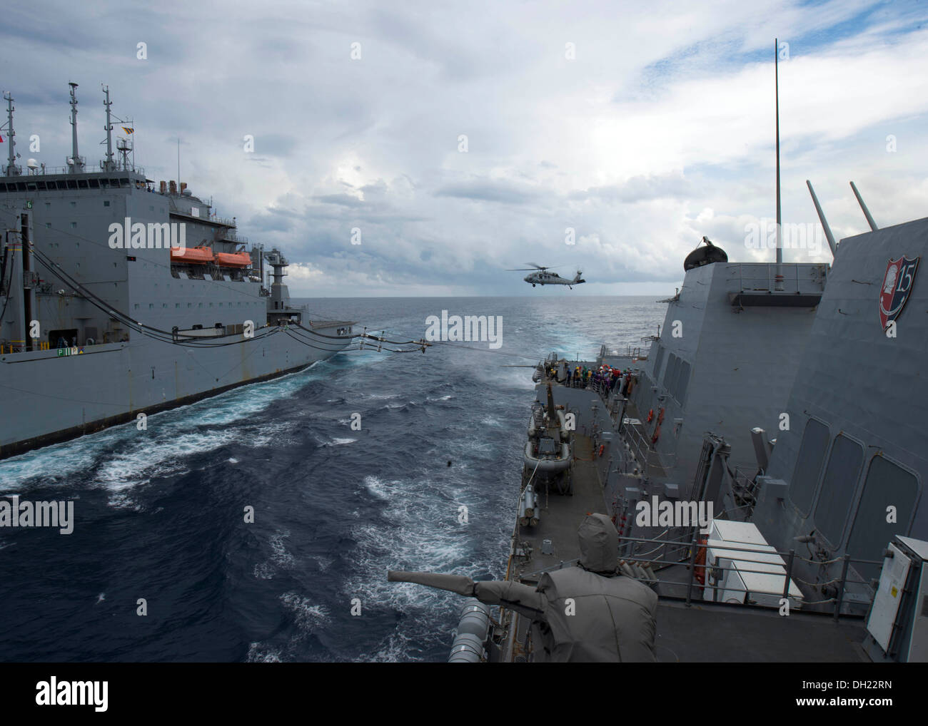 SOUTH CHINA SEA (Oct. 23, 2013) The guided-missile destroyer USS Mustin (DDG 89) conducts a replenishment-at-sea with the Military Sealift Command Lewis and Clark-class dry cargo and ammunition ship USNS Charles Drew (T-AKE 10). Mustin is on patrol with t - Stock Image