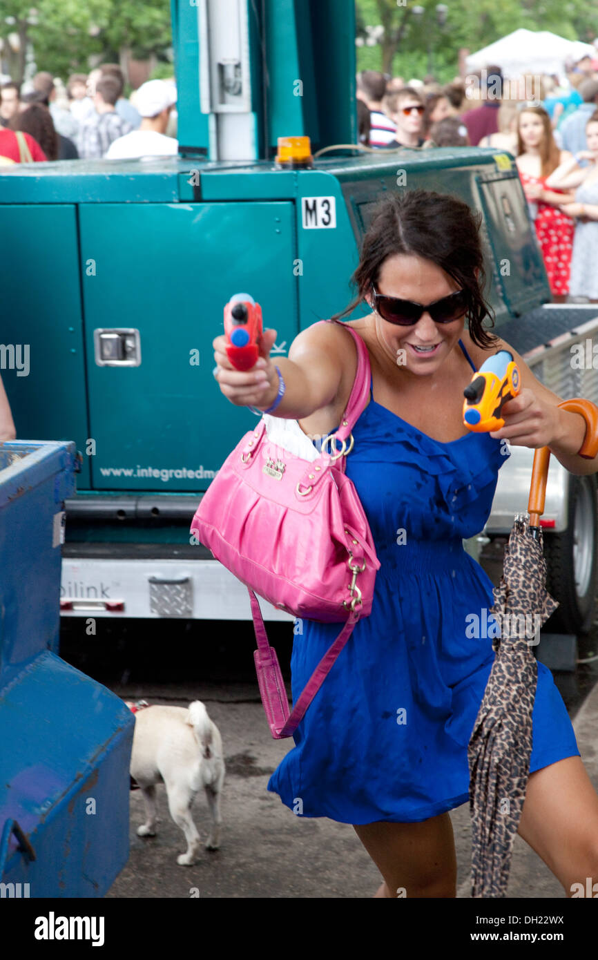 Woman with squirt guns in each hand. Grand Old Day Festival St Paul Minnesota MN USA - Stock Image