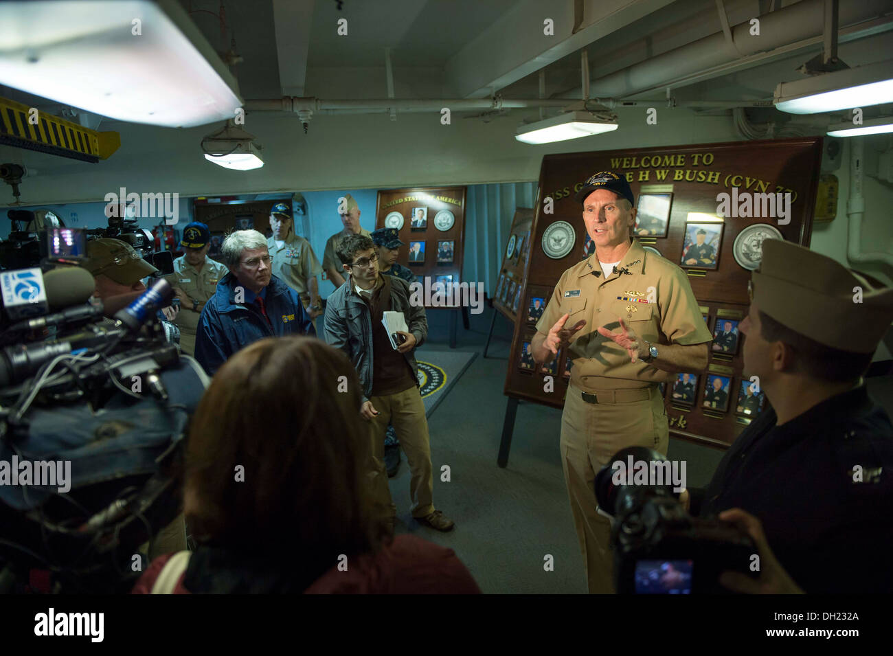 NORFOLK (Oct. 23, 2013) Chief of Naval Operations (CNO) Adm. Jonathan Greenert talks with local media after holding an all-hands call aboard the aircraft carrier USS George H.W. Bush (CVN 77) with Master Chief Petty Officer of the Navy (MCPON) Mike Steven - Stock Image