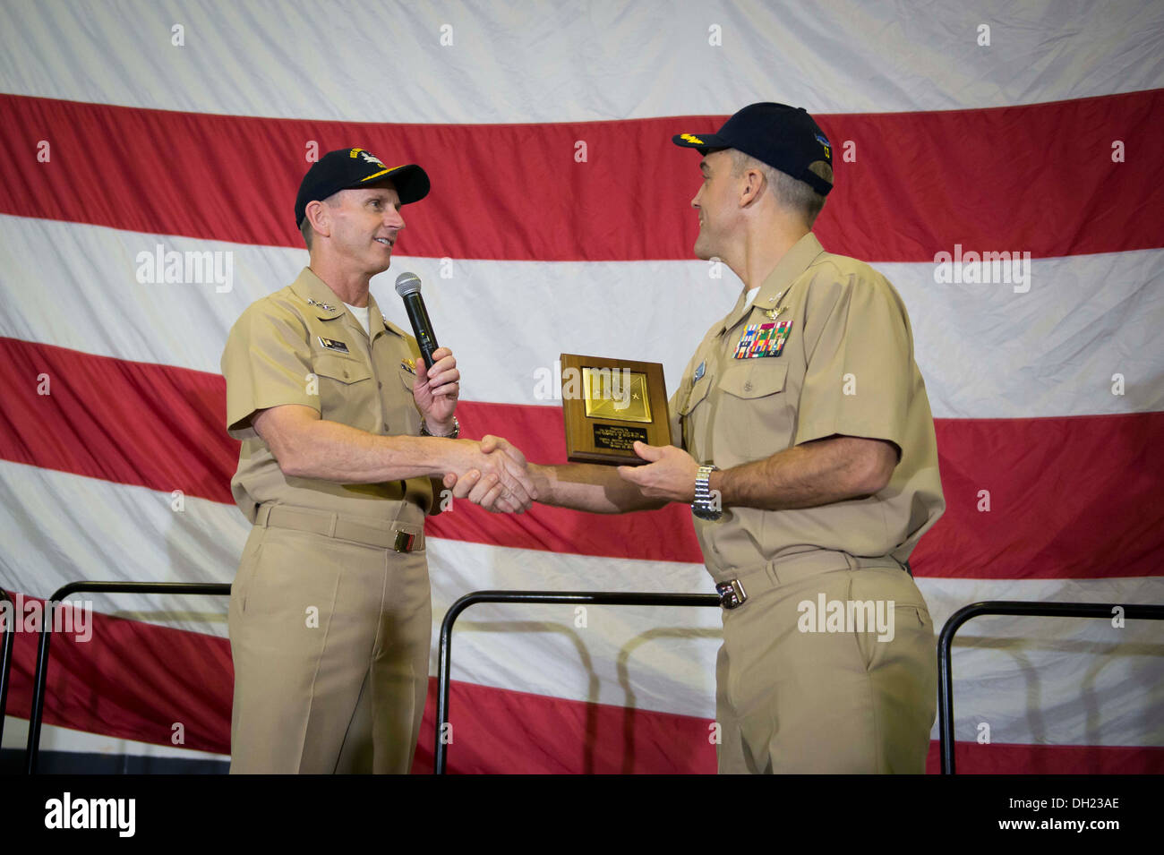 NORFOLK (Oct. 23, 2013) Chief of Naval Operations (CNO) Adm. Jonathan Greenert gives a plaque to Capt. Andrew Loiselle, commanding officer of the aircraft carrier USS George H. W. Bush (CVN 77) after he and Master Chief Petty Officer of the Navy (MCPON) M - Stock Image