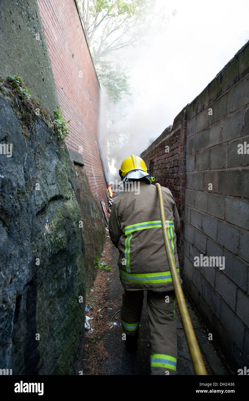 Fireman in alleyway tackling rubbish fire. FULLY MODEL RELEASED - Stock Image
