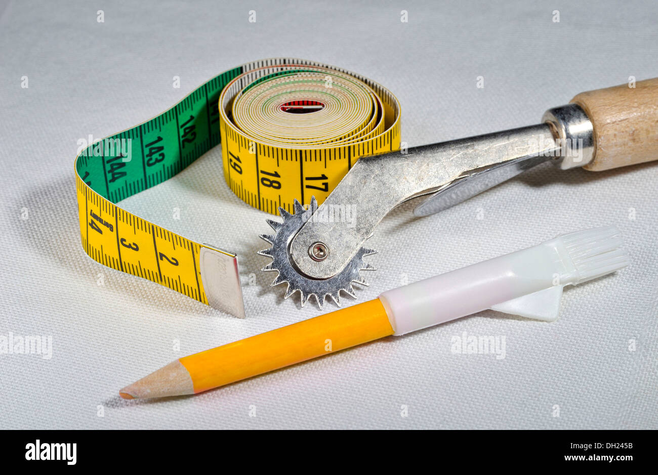 Seam roller, tape measure and white tailor's chalk lying on linen fabric Stock Photo