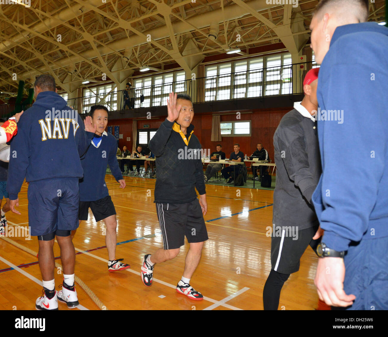 MISAWA AIR BASE, Japan (Oct. 26, 2013) Navy Misawa Chief Petty Officer Association members high-five members of the Japan Air Self-Defense Force at the 12th Annual Northern Air Defense Force Commanders Cup Tug-of-War Tournament, Oct. 26, 2013. This annual - Stock Image