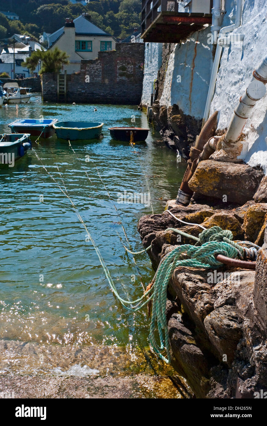 Rowing boats with ropes tied to steps at  water edge in village harbor Polperro Cornwall - Stock Image