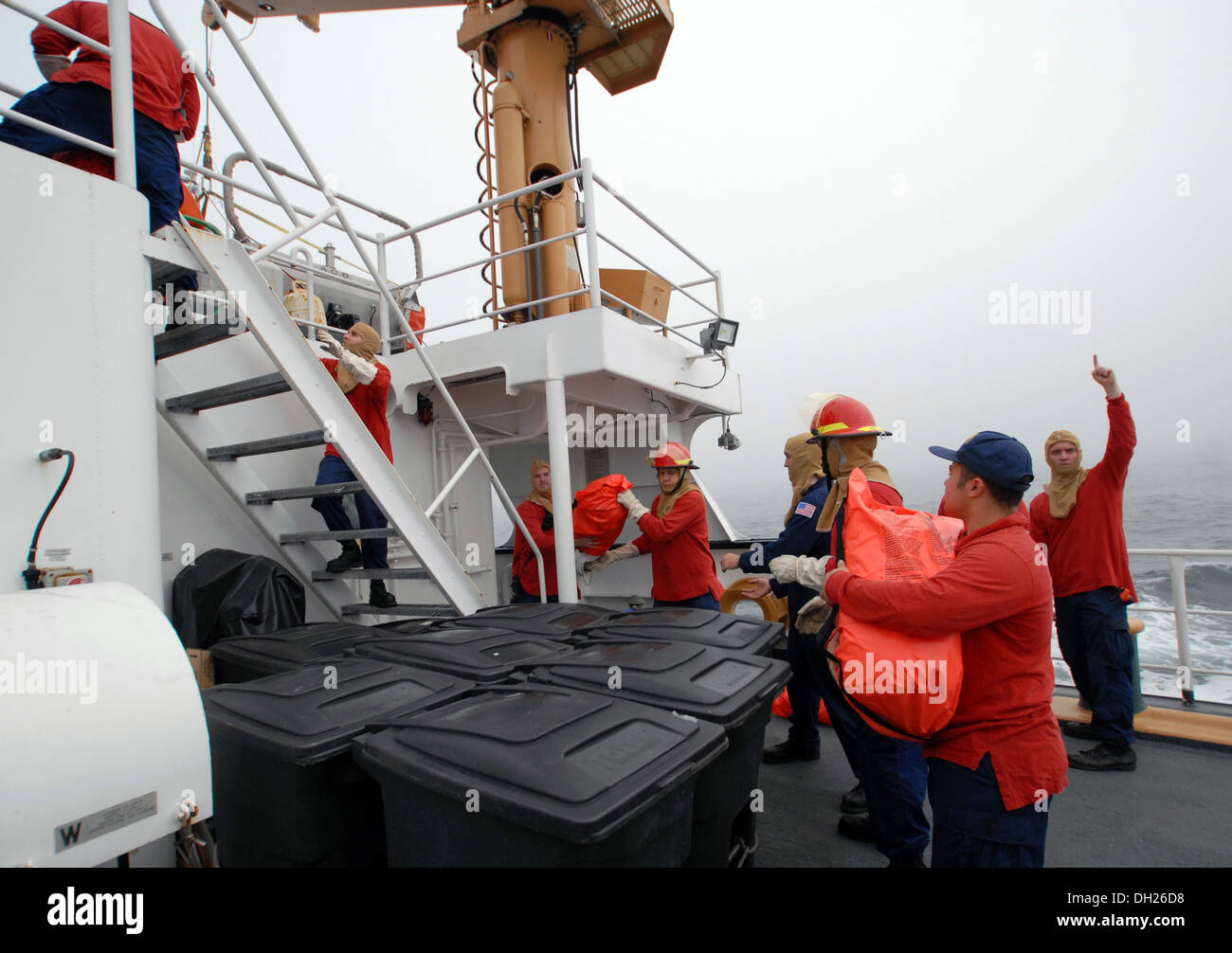 Members of USCG Cutter Hollyhock's crew work together to distribute survival suits during an abandon ship drill, Stock Photo