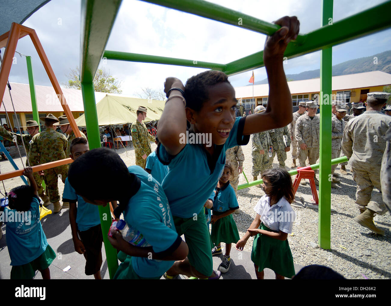 METRINARO, Timor-Leste – (Oct. 28, 2013) A local Timorese child is the first to conquer the monkey bars at his school's Stock Photo