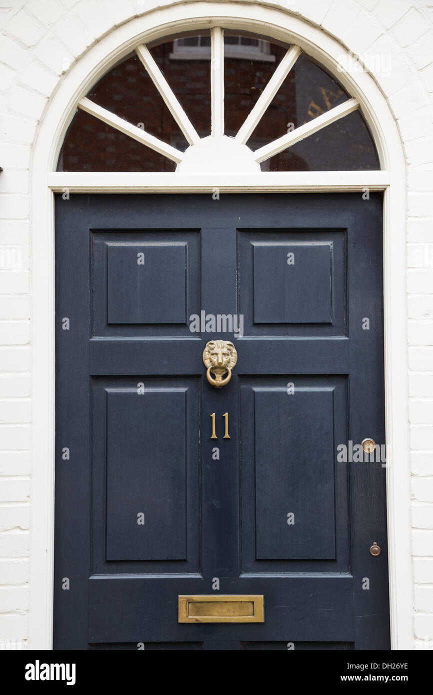 Front door - detail of traditional English house with brass lion door knocker brass letter box and a brass number 11 & Front door - detail of traditional English house with brass lion ...