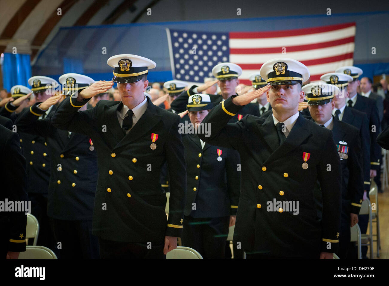 Officer candidates salute during the playing of the national anthem at an Officer Candidate School (OCS) graduation ceremony at - Stock Image