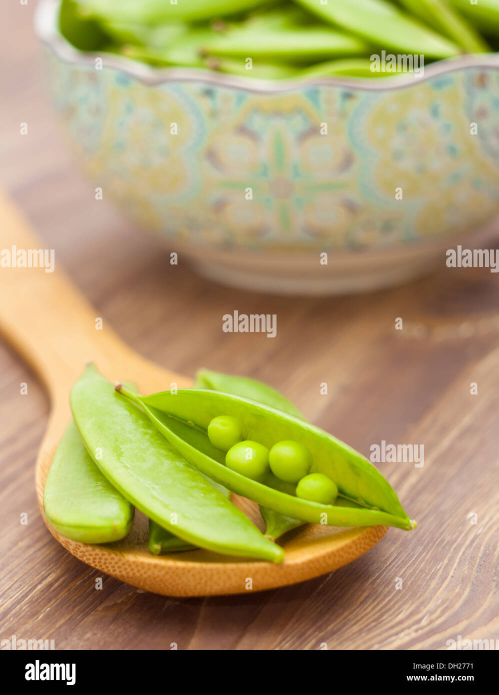 Pea pods on spoon, wooden background - Stock Image