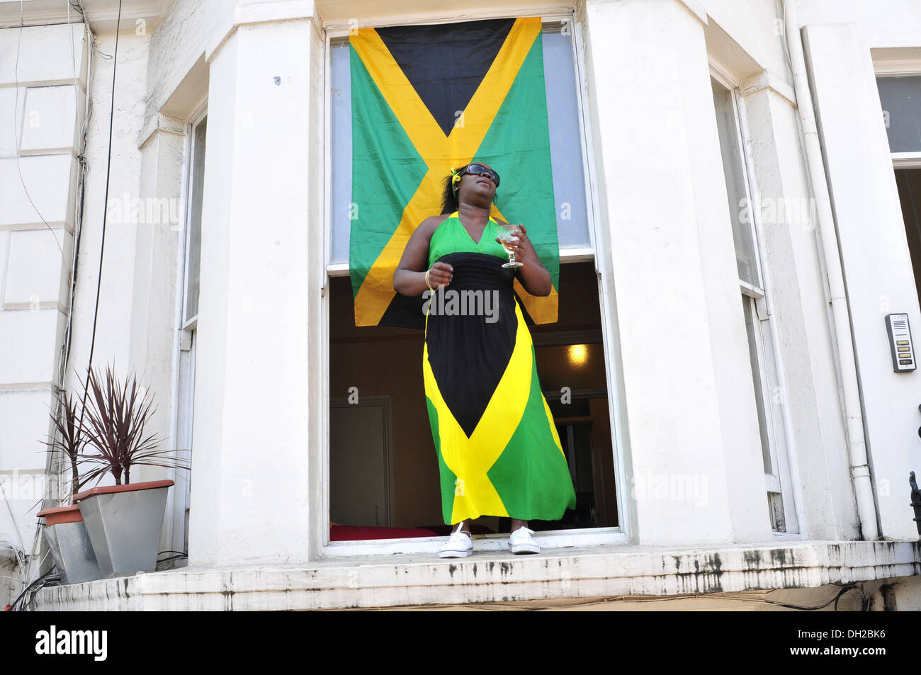 A woman wearing a Jamaican flag dress at the Notting Hill Carnival, London Stock Photo