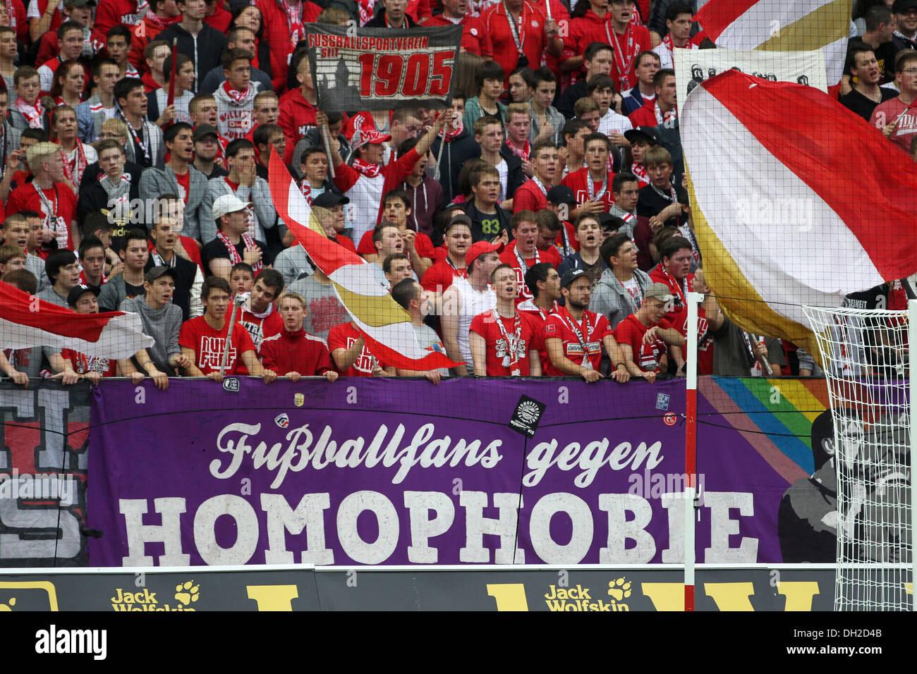 Fans of FSV Mainz 05 football club showing a banner 'Fussballfans gegen Homophobie', German for 'football fans against - Stock Image