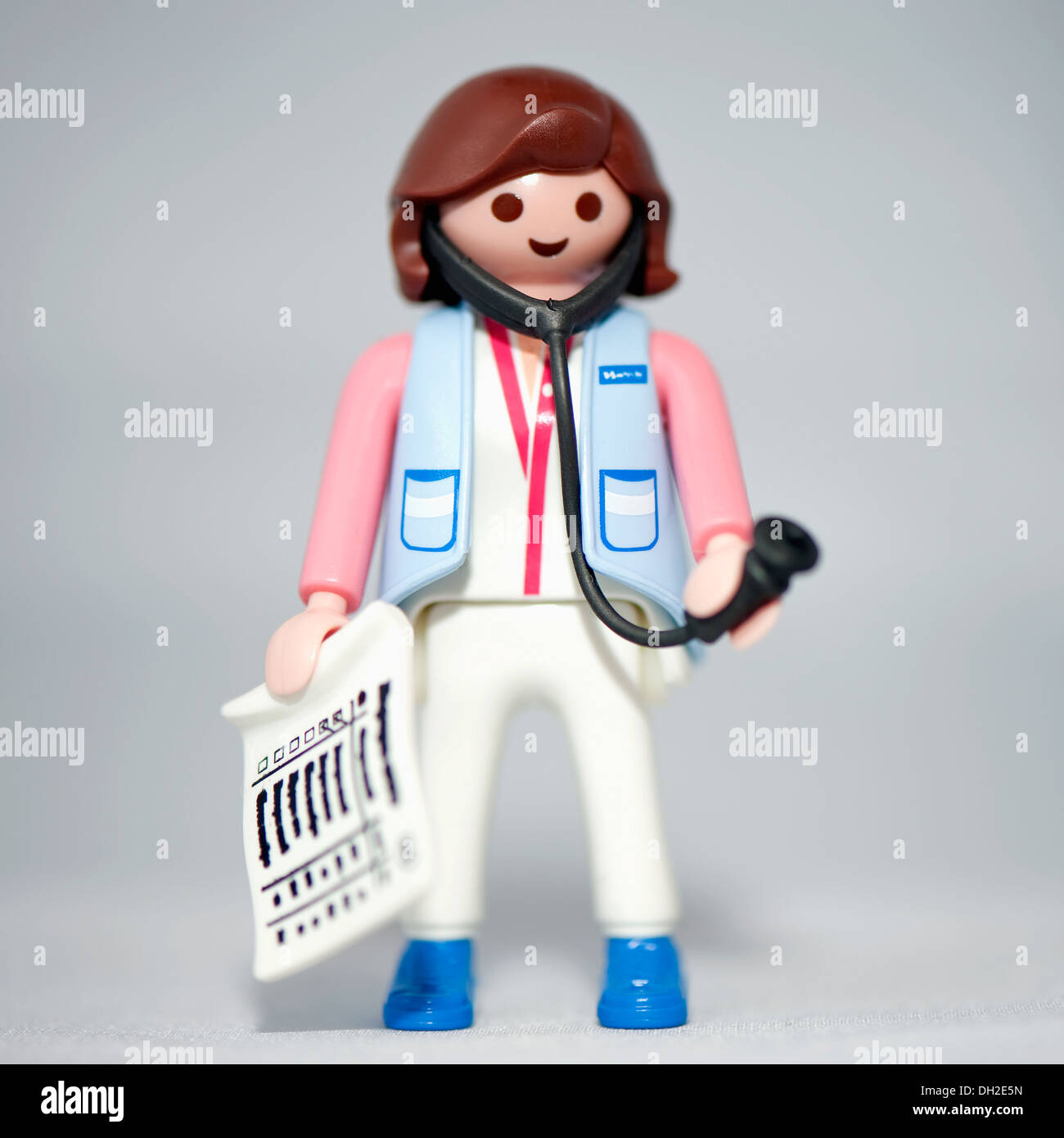 Close-up of a toy doctor figure holding a stethoscope. - Stock Image
