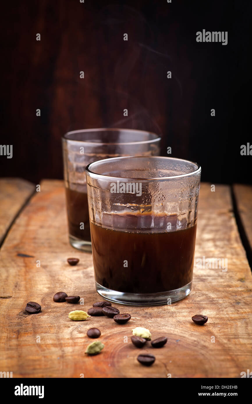 coffee in glass and ingredients on wood background - Stock Image