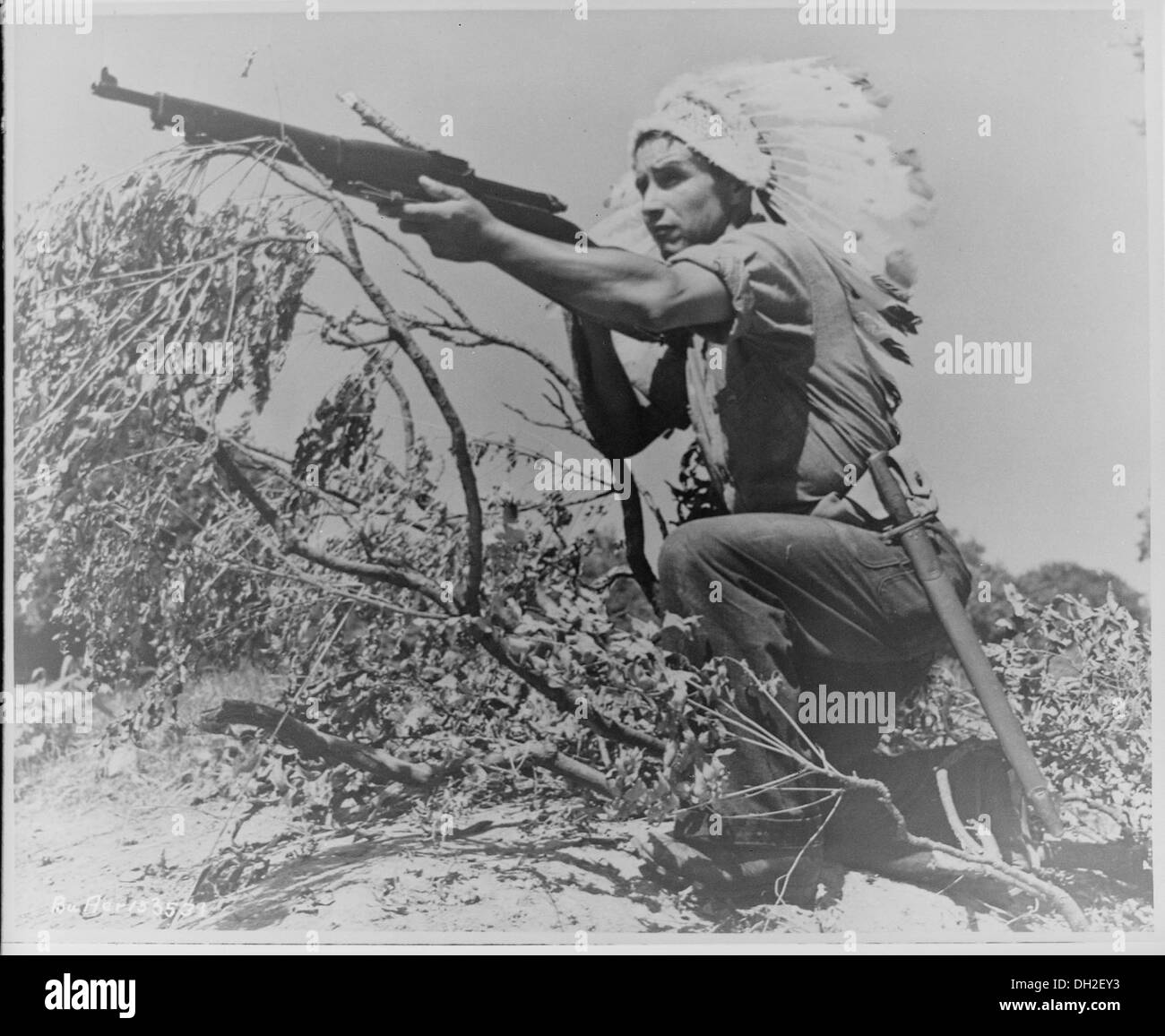 Dan Waupoose, a Menomini chief, full-length, kneeling with a rifle and wearing a feathered headdress, Algiers, Lousiana, 520636 - Stock Image