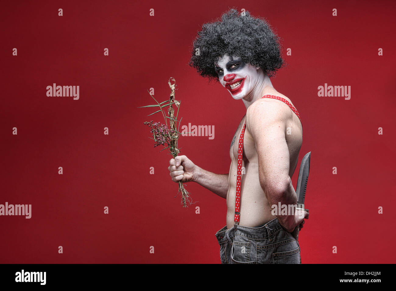 Evil Spooky Clown Portrait on Red Background - Stock Image