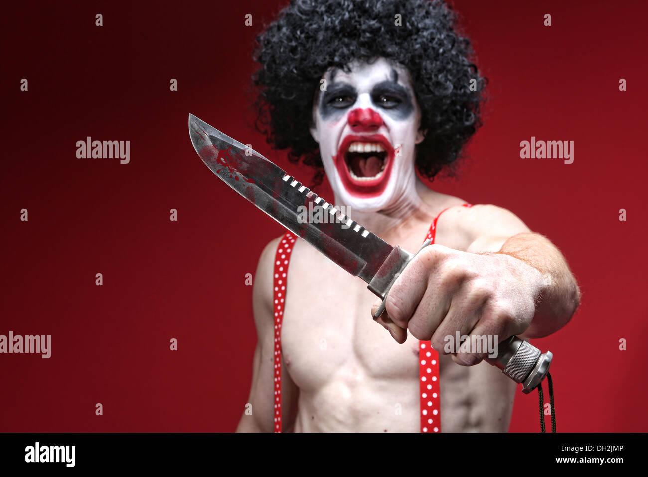 Evil Spooky Clown Portrait Holding Knife - Stock Image