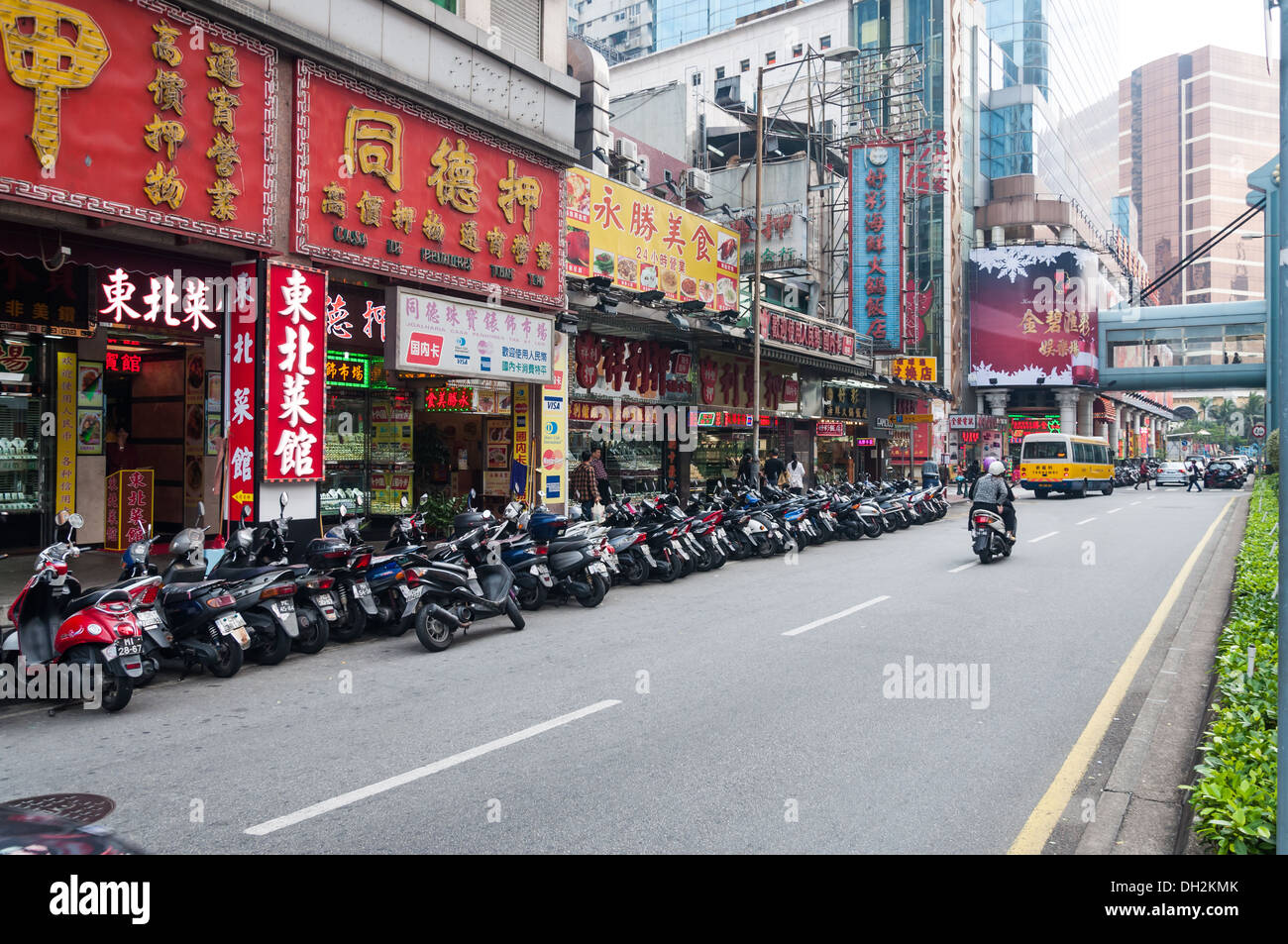 A long row of scooters on a street in Macau. - Stock Image