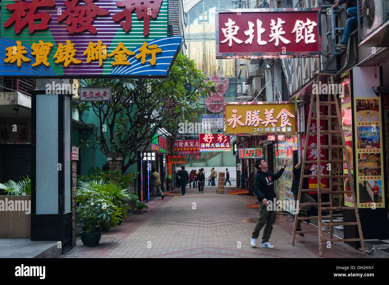 Men hanging advertisements in Macau, China. - Stock Image