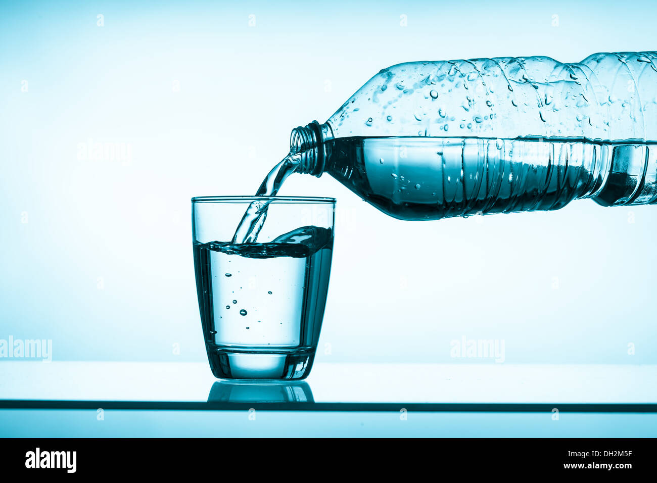 bottled water and a glass - Stock Image