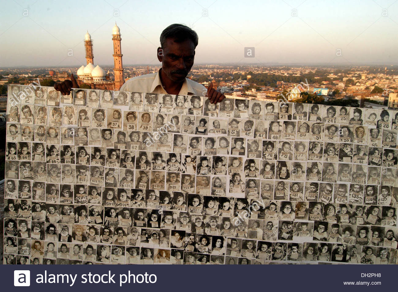 man showing holding photos of dead people from union carbide dow chemical poisonous gas leak bhopal madhya Pradesh India Asia - Stock Image
