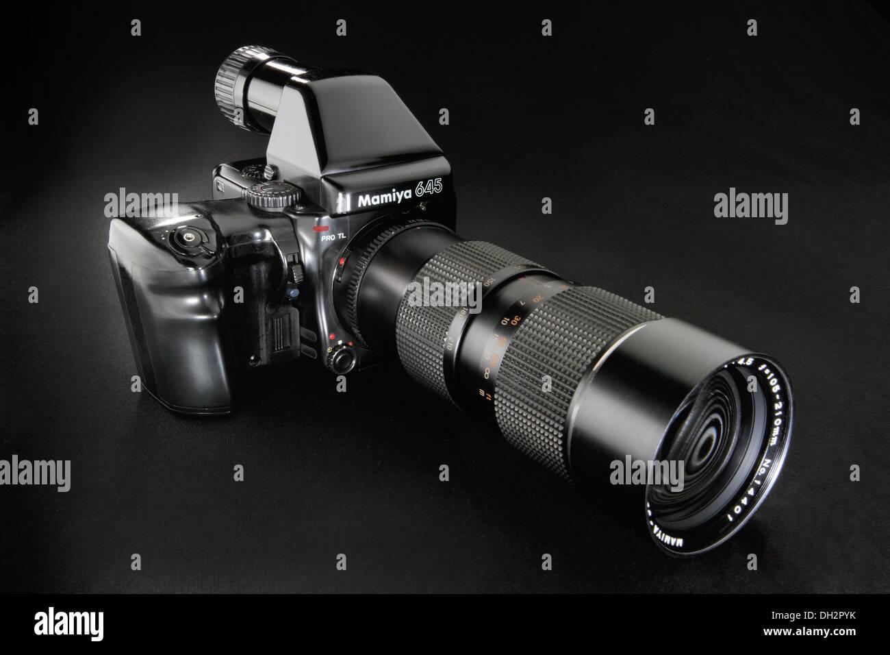 Film camera Mamiya 645 with long tele lens on black background - Stock Image