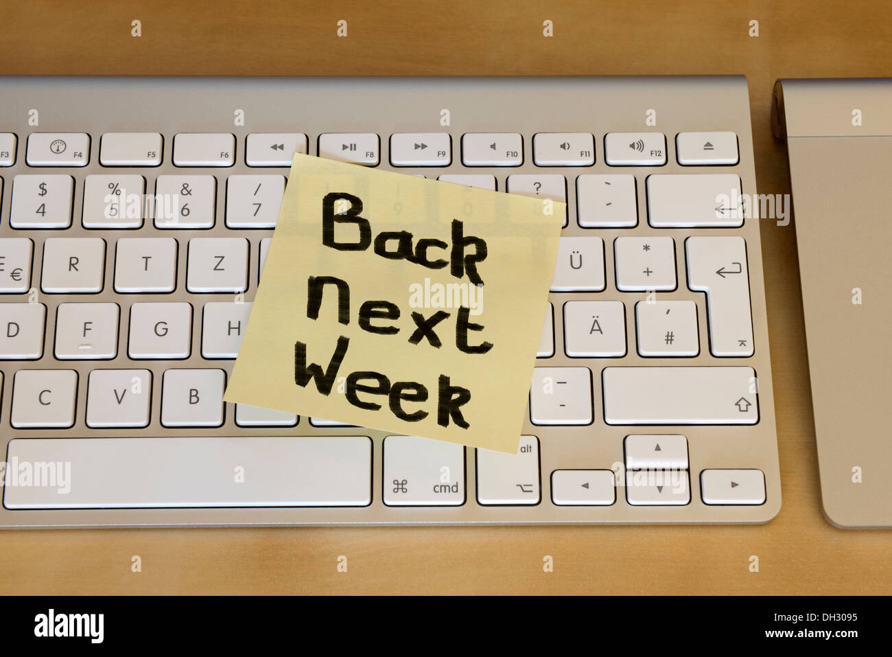 'Back next week' post it note on computer keyboard - Stock Image