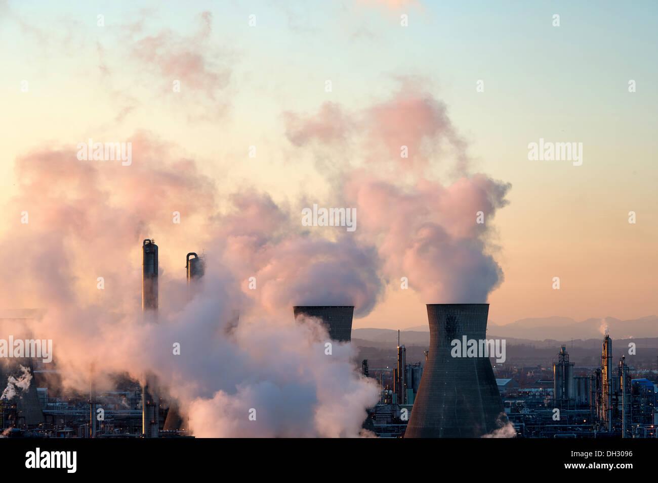 Grangemouth oil refinery chimneys spewing smoke in atmosphere, sunset coloring vapors in pink - Stock Image